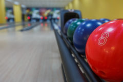 Bowling balls return machine, alley background. Bowling background. Interior of bowling alley lane with balls return machine closeup, selective focus on red ball Royalty Free Stock Photo