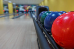 Bowling balls return machine, alley background. Bowling background. Interior of bowling alley lane with balls return machine closeup, selective focus on red ball Stock Photos