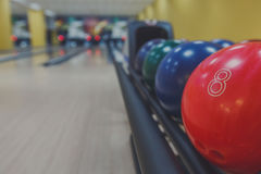 Bowling balls return machine, alley background. Bowling background. Interior of bowling alley lane with balls return machine closeup, selective focus on red ball Royalty Free Stock Image