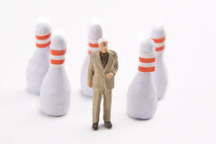 Bowling for Business. Miniature business man with bowling pins Royalty Free Stock Photography
