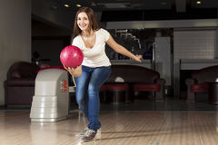 At bowling club. Young pretty woman throwing a bowling ball royalty free stock photos