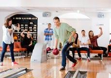 Bowling d'homme avec des amis encourageant dans le club Photo stock