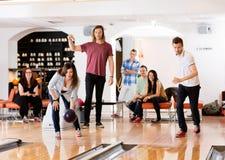 Bowling d'homme et de femme avec des amis à l'arrière-plan Image stock