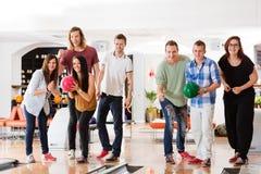 Bowling d'homme et de femme avec des amis dans le club Photographie stock libre de droits