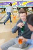 Bowling d'homme tandis que les amis ont la boisson Photo libre de droits
