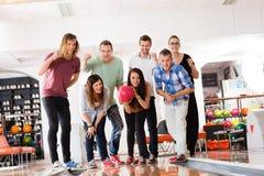 Bowling de femme tandis qu'amis motivant dans le club Photo libre de droits