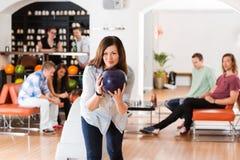 Bowling de jeune femme dans le club Image stock