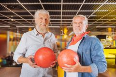 Joyful nice men standing together with balls. Bowling fans. Joyful nice men standing together while holding bowling ball royalty free stock photos
