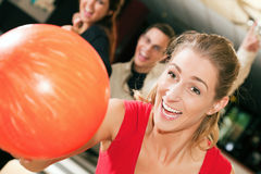 Bowling with friends. Group of four friends in a bowling alley having fun, three of them cheering the one in charge to throw the ball royalty free stock photo