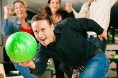 Bowling with friends. Group of four friends in a bowling alley having fun, three of them cheering the one in charge to throw the ball Royalty Free Stock Images