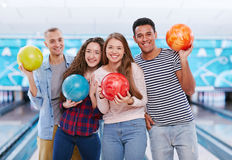 Bowling fun. Group of joyful young friends with bowling balls looking at camera stock image