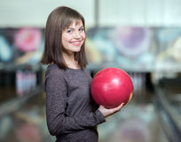 Bowling Game. Young beautiful smiling girl playing bowling Royalty Free Stock Photos