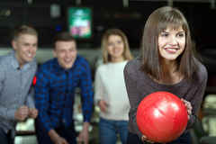 Bowling Game. Group of four friends in a bowling alley having fun, three of them cheering the one girl in charge to throw the bowling ball Stock Image