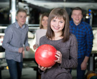 Bowling Game. Group of four friends in a bowling alley having fun, three of them cheering the one girl in charge to throw the bowling ball Royalty Free Stock Photography