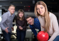 Bowling Game. Group of four friends in a bowling alley having fun, three of them cheering the one girl in charge to throw the bowling ball Stock Photography