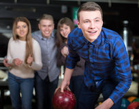Bowling Game. Group of four friends in a bowling alley having fun, three of them cheering the one in charge to throw the bowling ball Stock Photos