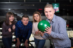 Bowling Game. Group of four friends in a bowling alley having fun, three of them cheering the one in charge to throw the bowling ball Royalty Free Stock Photos