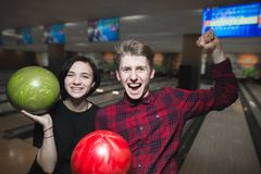 Bowling game. Happy young people with bowling balls lifted their hands upward with joy. Bowling players have won royalty free stock photos