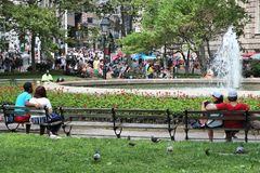 Bowling Green park. NEW YORK, USA - JULY 4, 2013: People visit Bowling Green park in New York. The park dates back to 1733 and is listed on U.S. National Stock Image
