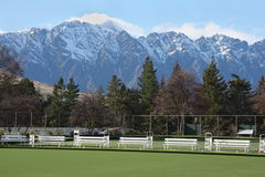 Bowling green with a view. Bowling green with view of snow capped mountains Royalty Free Stock Photo