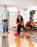 Bowling heureux de jeune femme dans le club Images libres de droits
