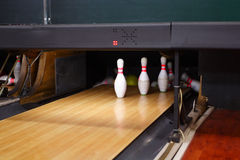 Bowling lane and skittles. Partially knocked down set of bowling skittles on wooden bowling lane Royalty Free Stock Images