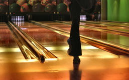Bowling lanes. In the foreground there is a bowler's leg, a rolling ball next to it, shallow DOF Stock Photography