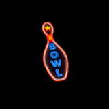 Bowling Pin Neon. A glowing neon sign featuring a bowling pin with the word BOWL isolated on black Stock Photo