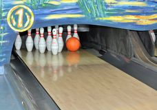 Bowling pins and ball. Orange bowling ball about to hit the pins stock photography