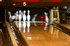 Bowling pins falling from ball. Bowling pins being knocked down at an alley by a a ball. Slow shutter speed royalty free stock image
