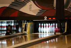 Bowling pins falling from ball. Bowling pins being knocked down at an alley by a a ball. Slow shutter speed royalty free stock photography