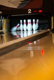 Bowling pins falling from ball. Bowling pins being knocked down at an alley by a a ball. Slow shutter speed stock photo