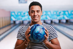 Bowling player. Handsome young man with bowling ball stock images