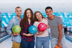 Bowling players. Friendly guys and girls holding bowling balls stock photo