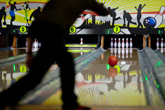 Bowling. Rolling to the pins. Underexposed silhouette of men bowling Stock Photos
