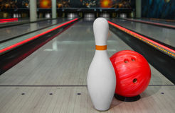 Bowling skittles and ball for bowling game. On the gaming track on the background of bowling Stock Photos