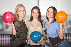 Bowling. Smiling group of female friends bowling and are holding balls royalty free stock photo
