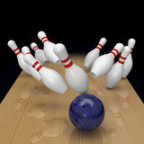 Bowling a strike on black background Royalty Free Stock Images