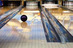 Bowling. Swirling bowling ball is rolling down the path to the bowling pins stock photo