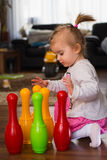 Bowling toys. Baby girl 1,5 years old playing on a floor in living room Stock Photography
