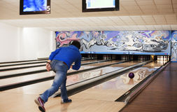Bowling. Young man rolling bowling ball Stock Images