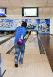 Bowling. Young man rolling bowling ball royalty free stock image
