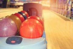 Bowlingkugeln auf dem Hintergrund der Bahnen im Bowlingspiel schlagen mit einer Keule Lizenzfreies Stockfoto
