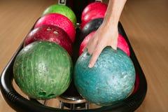 Bowlingspielkugel in der Spielermannhand Lizenzfreies Stockfoto