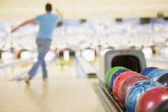 Bowlingspielkugelmaschine mit Mannbowlingspiel Lizenzfreies Stockfoto