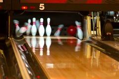 Bowlingspielstifte, die von der Kugel fallen Lizenzfreies Stockbild