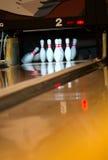 Bowlingspielstifte, die von der Kugel fallen Stockfoto