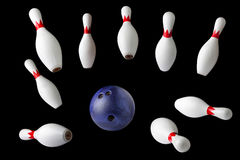 Bowlingspielstifte und -ball lokalisiert auf schwarzem Hintergrund Stockbild