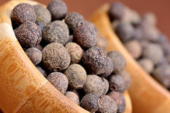 Bowls with allspice on brown background. Closeup royalty free stock photos