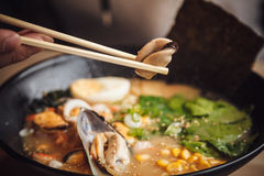 Bowls of Asian soup with seafood, eggs, onion Royalty Free Stock Images